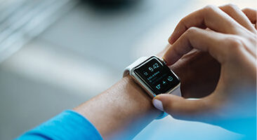 Anticipating launch: Stock image of trainer / client checking wrist watch / heart rate monitor.
