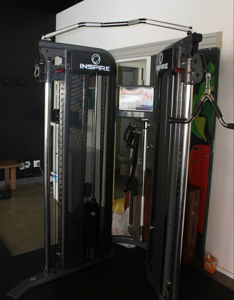 The IFFT Inspire functional trainer. TrainingSpaces emphasizes flexible, adaptable equipment; by positioning the handles at various heights and changing the angle and degree of motion, the user can emphasize many different muscle groups and work toward the desired results in relative comfort.