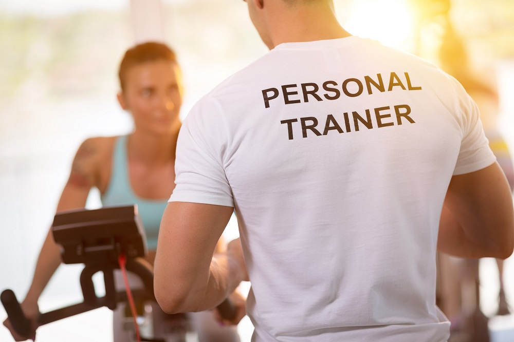 Personal trainer coaching client on stationary bike. Image credit: Universal Training Academy