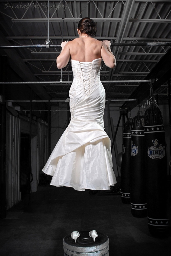 Woman in bridal gown doing pull-ups