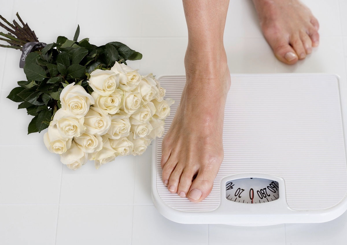 Foot on scale with flowers for weight loss post