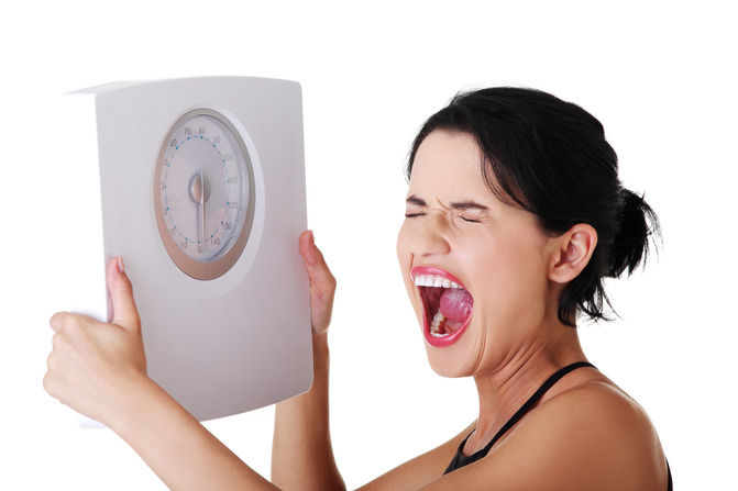woman holding scale and screaming because she's hit a plateau. Image credit: diyhcg.com