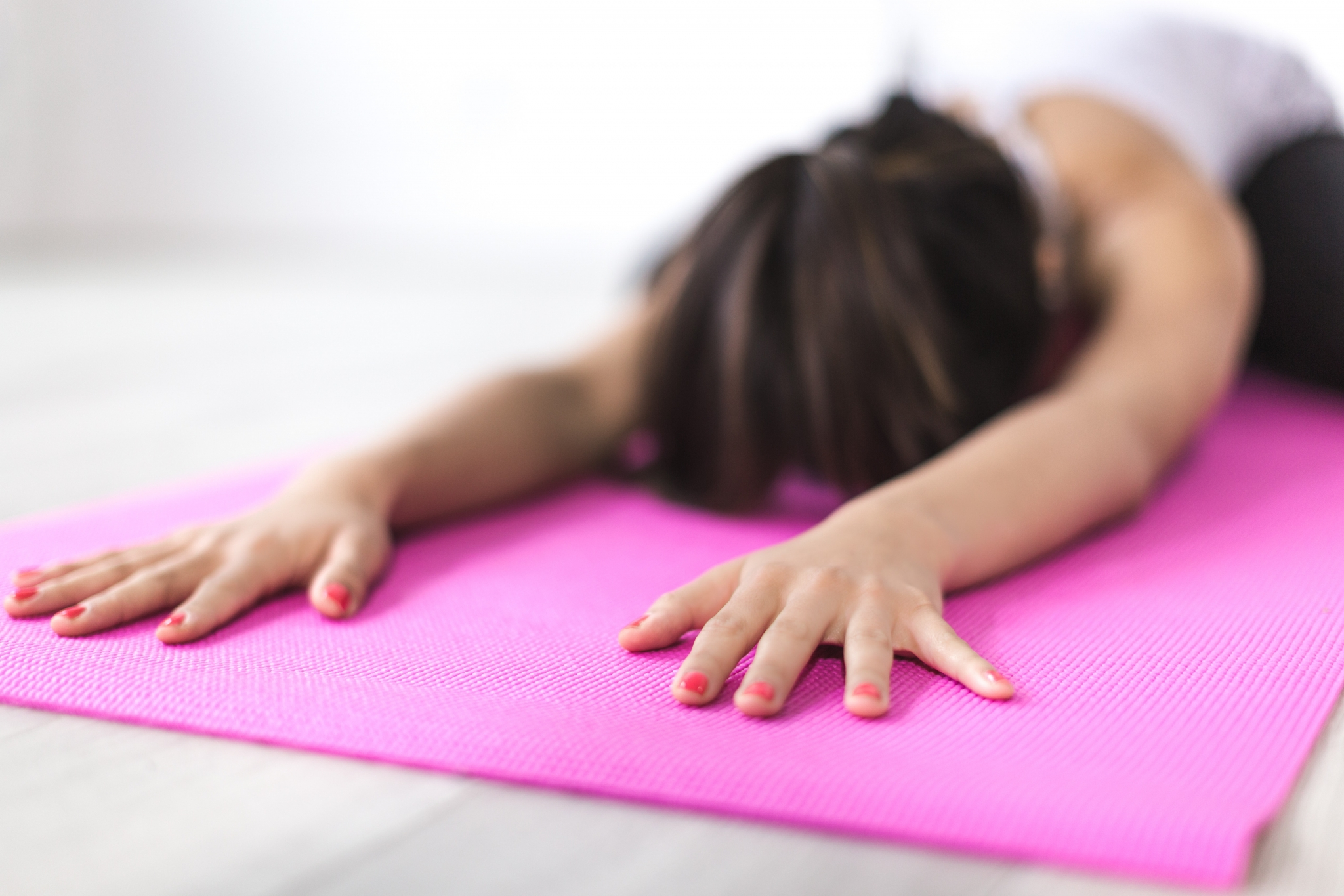 woman on pink yoga mat with hands extended