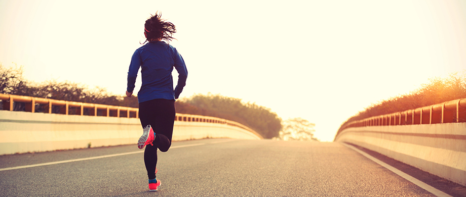 Smart fitness goals: woman running across a bridge. Image credit: SoPosted.com