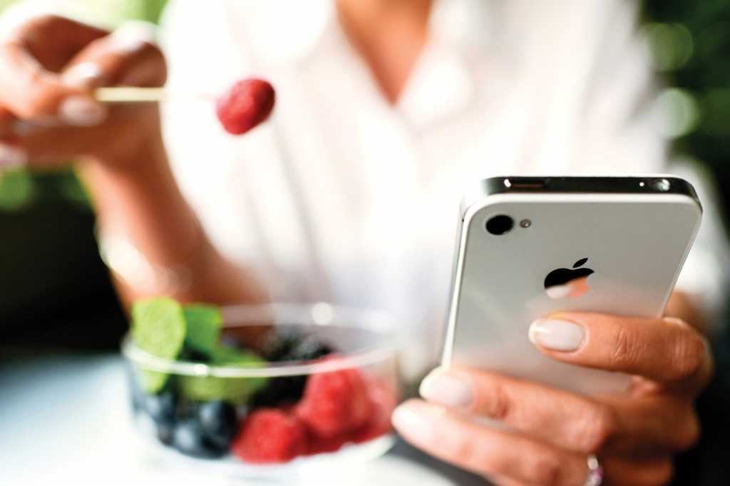 Woman eating fruit and using food tracks dessert with iPhone 4s in hands