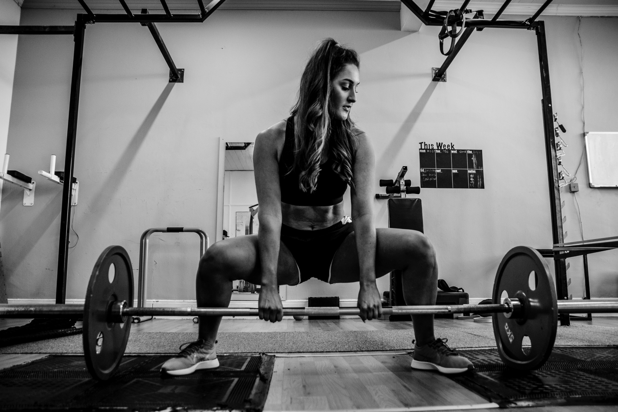 Black and white image of woman weight training / Photo by Derwin Edwards from Pexels