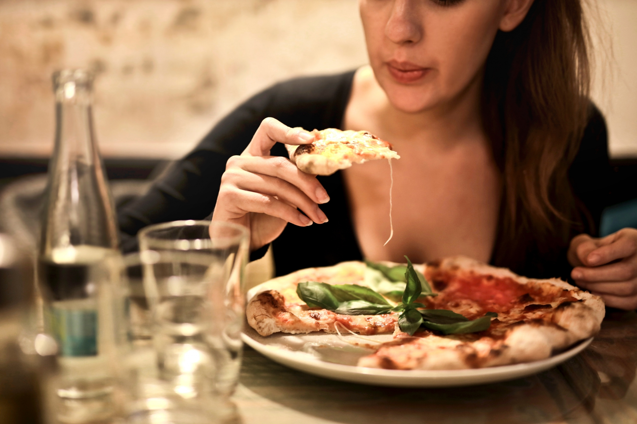 Woman eating thin crust pizza / Photo by bruce mars from Pexels