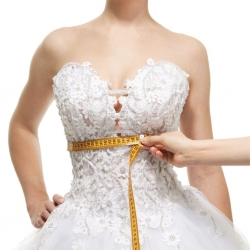 stock shot of tape measure around waist of woman in bridal gown